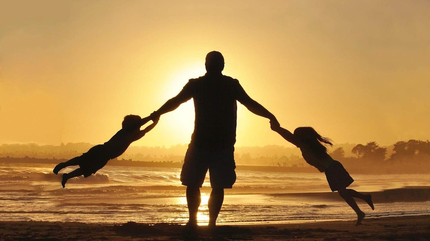 A silhouette of two young children swinging off their dad's arms on the beach.