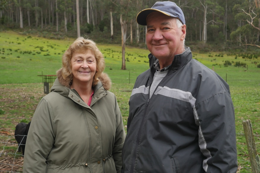 A man and woman in coats smile at camera as they stand in a grass paddock backed by tall eucalypts