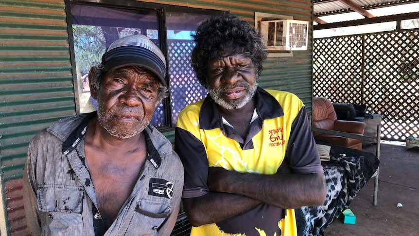 Two Indigenous men standing on the verandah of a house.