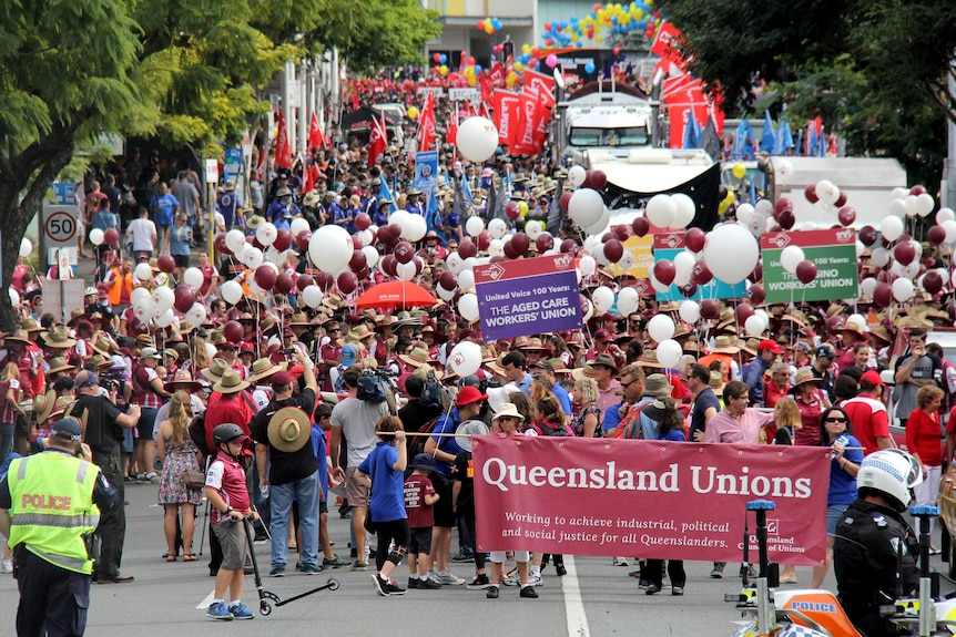 Thousands of union members with balloons and banners congregate together on a street.