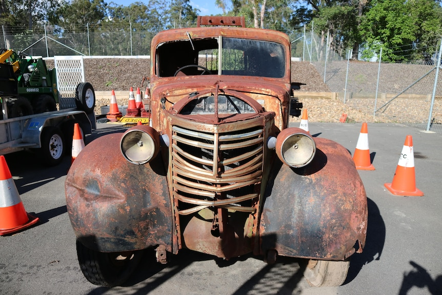 The front of a rusted, derelict Chevy truck.