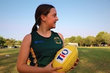 Isabell Dewsbury looks away from the camera holding a football wearing a St Mary's singlet at Nightcliff oval.