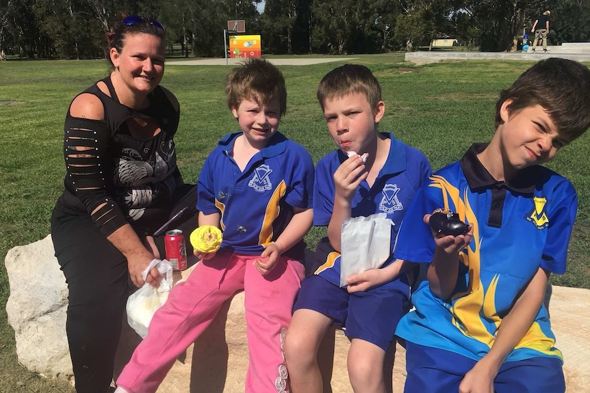 Suzie short sits at a park with her three primary school aged boys