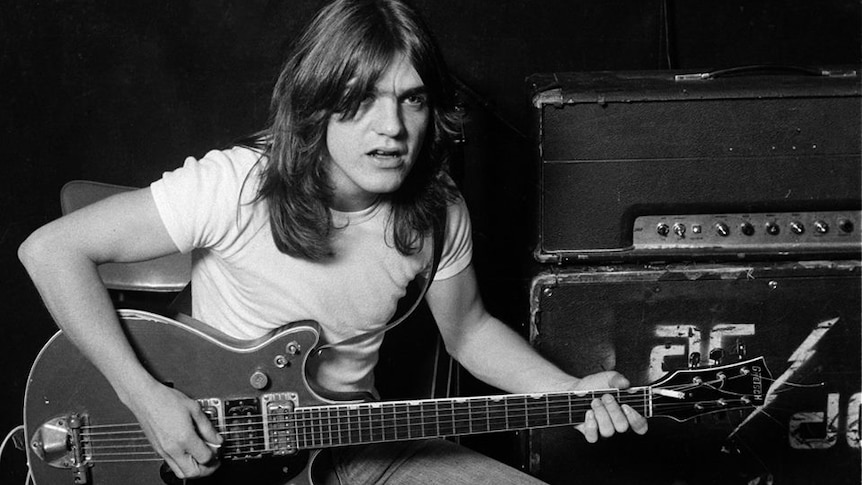 A young Malcolm Young holds a guitar as he poses, sitting on an amp
