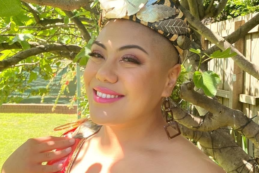 Woman stands under tree and smiles to camera, wearing a women floral headband and pink dress.