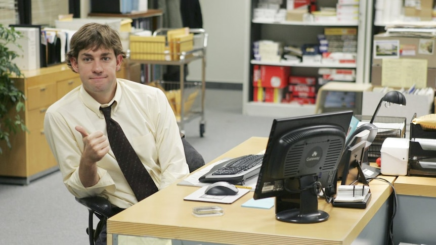 Jim Halpert from The Office sits casually at his desk with his tie loosened giving a thumbs-up