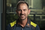 Justin Langer wears a blue and yellow shirt