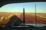 A view of a red highway stretching out from inside a ute