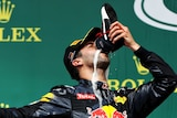Daniel Ricciardo drinks champagne out of his boot after the German Grand Prix