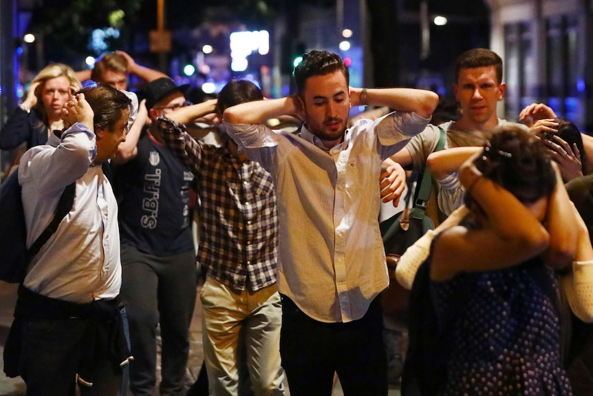 People leave the area with their hands up after an incident near London Bridge.