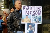 "Ross Grant holds a sign outside the DVA that reads: ""DVA killed my son"""