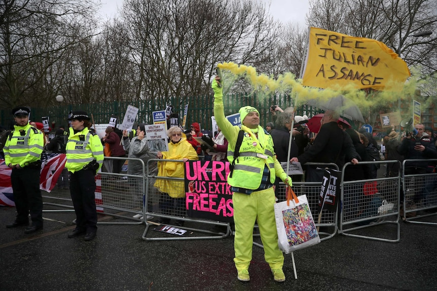 A demonstrator dressed in yellow, and holding a yellow smoke flare, stands in front of a crowd.