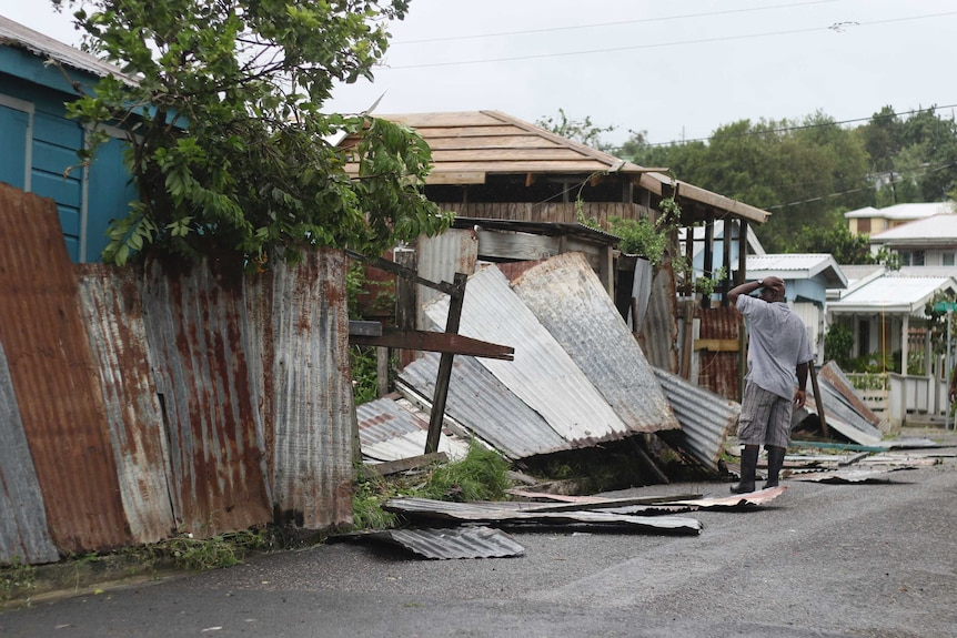A man surveys the wreckage on his property after the passing of HurricaneIrma