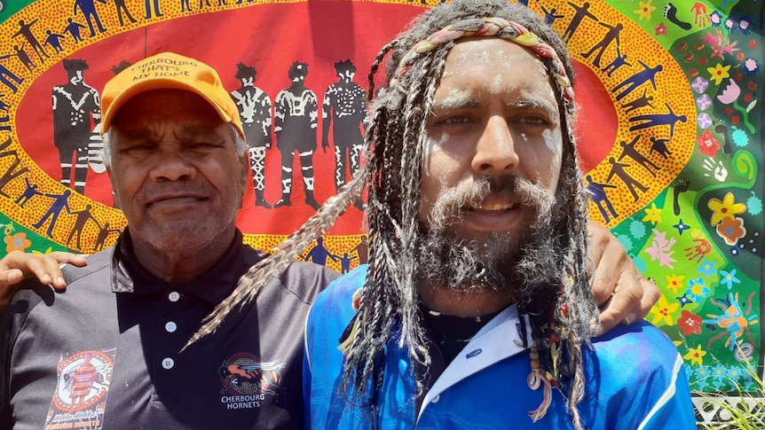 Two Indigenous man stand together with their arms around each other in front of a colourful banner.