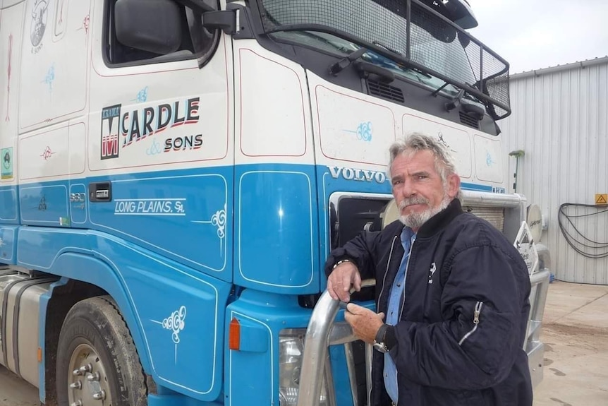 A man in front of a truck cab