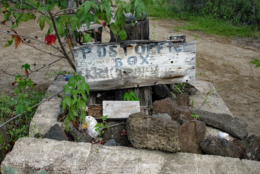 A close up of the post box in the Galapagos, built together with rocks and wood.