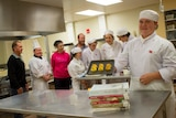 Glossop High School student Zoe Harrington stands with a tray of pastries in front of fellow students and staff.