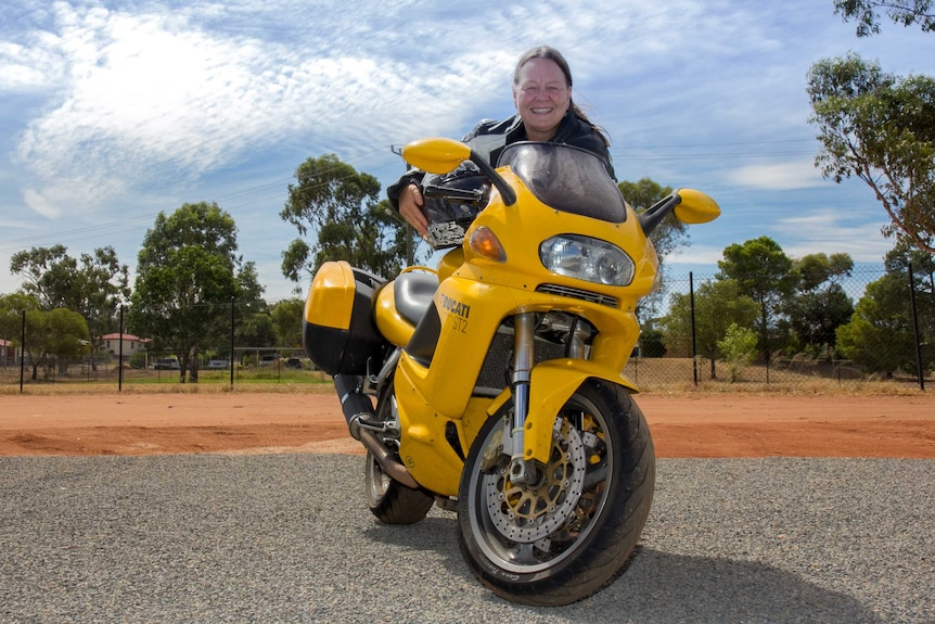 A woman holding a motorcycle helmet and leaning forward over a yellow motorbike