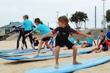 Students practice balancing on boards on the sand.