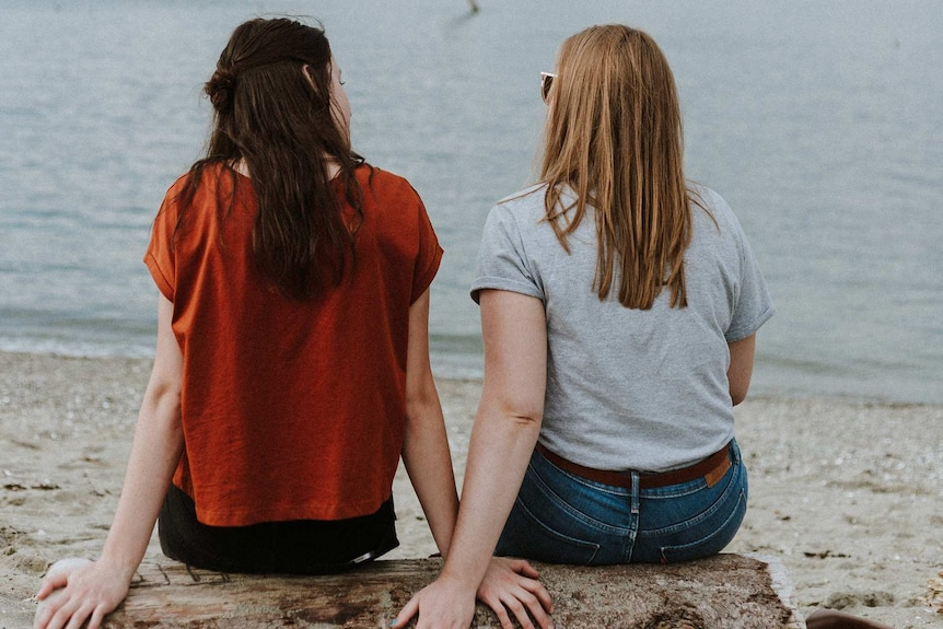 Two young women sit on the beach facing the ocean for a story about helping someone out of an abusive relationship.