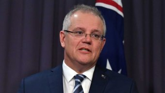 Scott Morrison looks to the right as he stands in front of a blue background mid-speech. An Australian flag is also behind him.