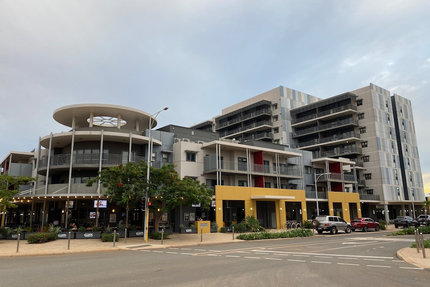 A low rise block of apartments with a round feature at the front stands in front of a taller block of apartments.
