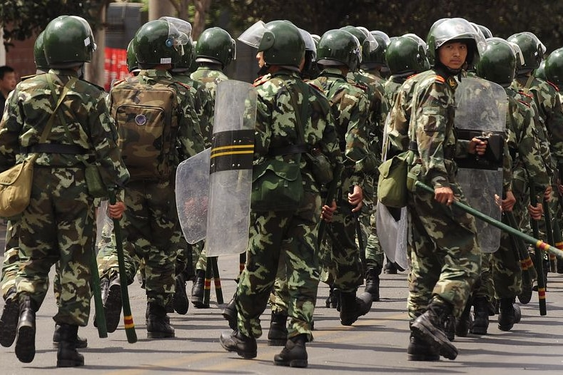Chinese riot police patrol a street in Urumqi