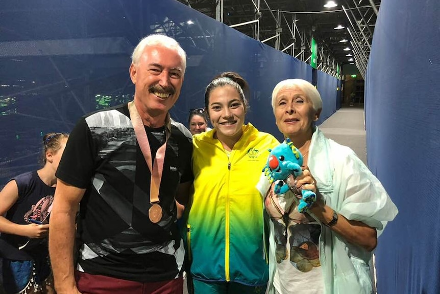 Three people smile and pose with a medal
