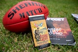 A football and Anzac Day chocolates and a magazine sit on grass.