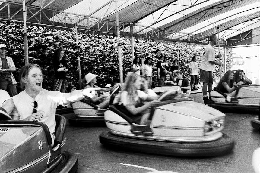 A black-and-white photo shows young people having fun on dodgem cars.