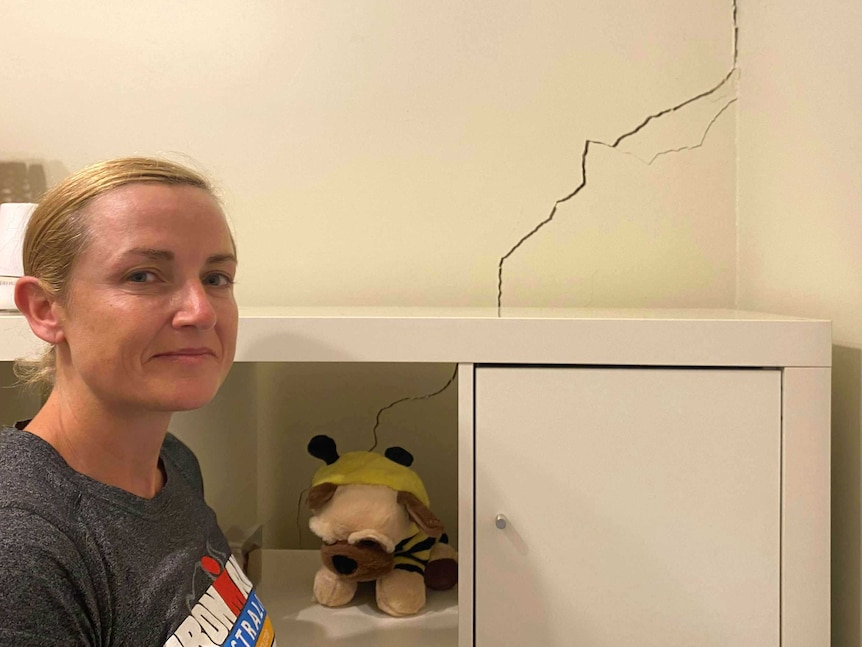 A woman stands in front of a bookcase and a cracked wall.