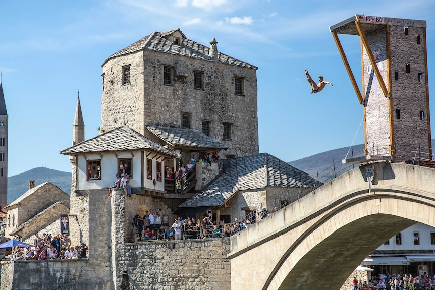 David Colturi of the US dives from the 27.5 metre platform on Stari Most as people watch.