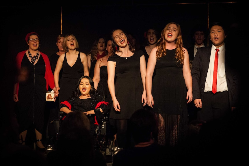 Elene men and women sing on a dark stage, wearing mostly black formalwear with red accents.