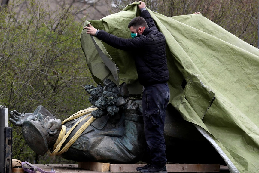 A man in a face mask covers a dark bronze statue of a man in military uniform with a tarp. The statue is on its back.