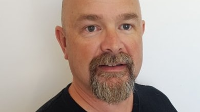 Corporate headshot of a bald, bearded man in a black T-shirt.