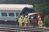 Police investigate a train carriage that's derailed amongst trees at night.