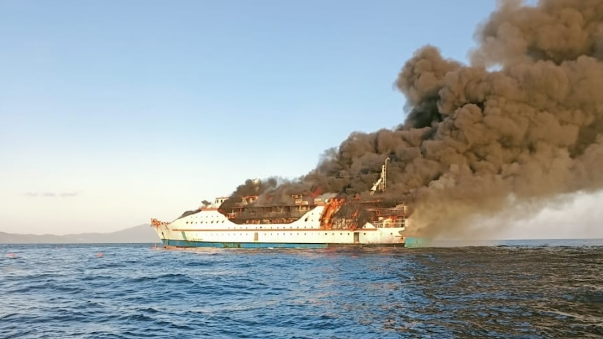 A ferry is in flames on the ocean.