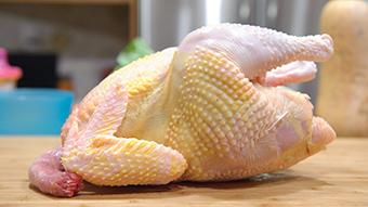 A raw chicken on a chopping board.
