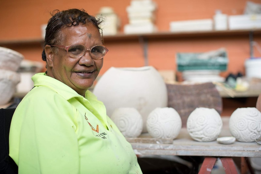 Aboriginal artist Michelle Yeatman smiles for a photograph in front of her pottery.
