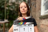 A young woman holding a clapper board