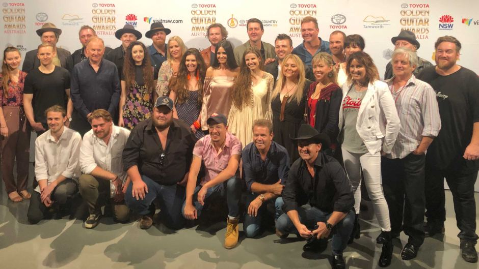 A large group of musicians pose for a group photo.