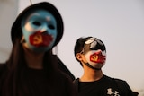 Two protesters wear masks with the Hong Kong, Communist party and East Turkestan symbol on them.