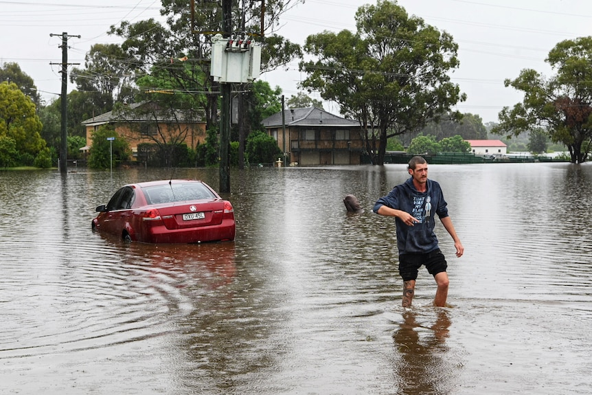 A man walks through flood water with a car in the background