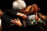 Labour Party members hug during Norway memorial