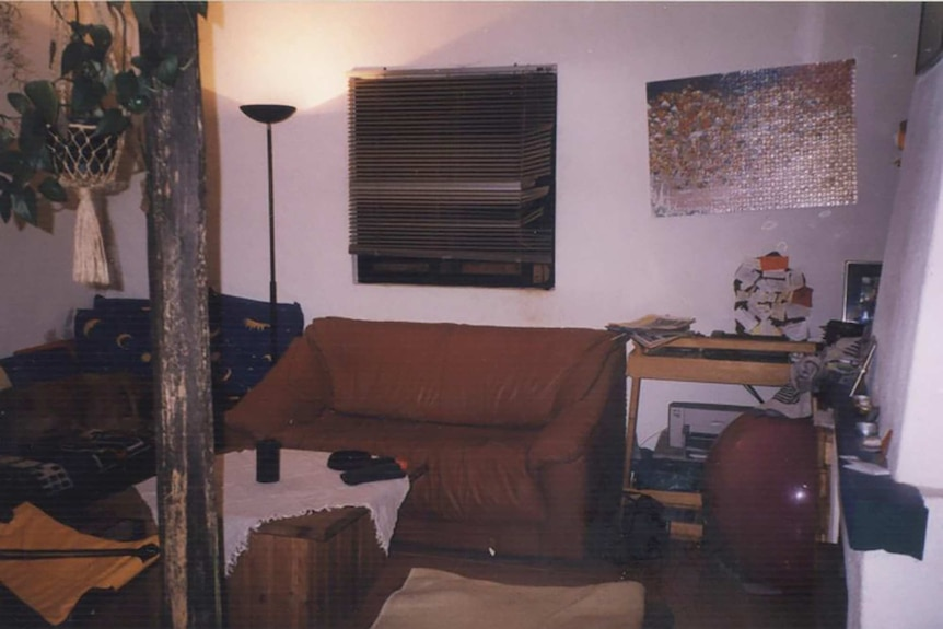 An interior of a house shows a couch, desks, a lamp, blinds, a table and a wall-mounted puzzle