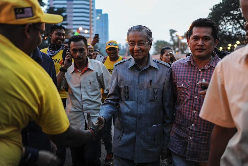 Former prime minister Mahathir Mohamad (C) shakes hands with supporters