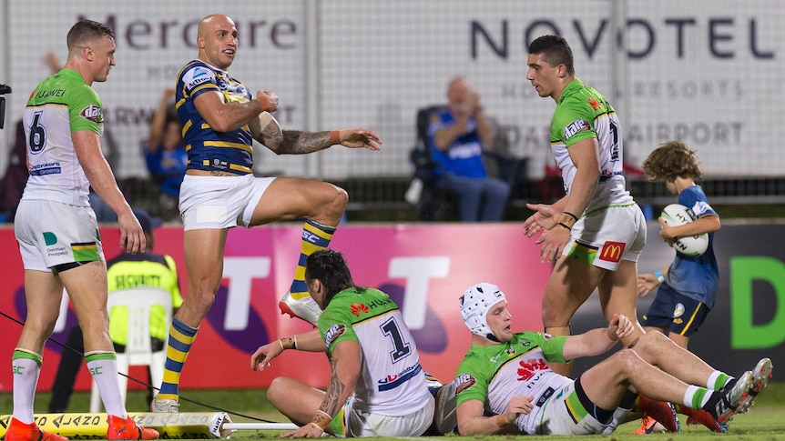 An NRL player dances in celebration after scoring a try.