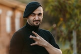 The Lebs book author Michael Mohammed Ahmad poses for a portrait wearing a black skivvy and beret doing a westside gang sign.