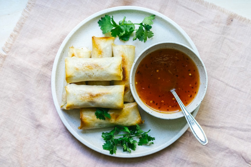A plate of baked vegetarian spring rolls with homemade sweet chilli sauceby Hetty McKinnon.