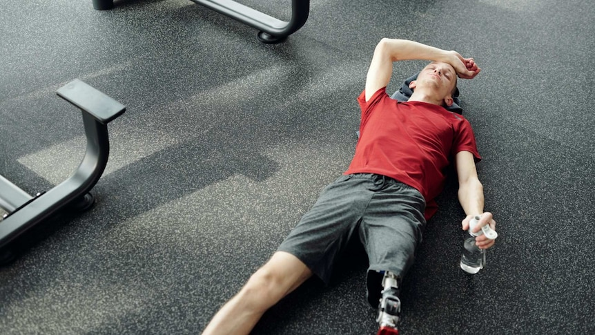 A man lying on the floor of a gym looking exhausted.